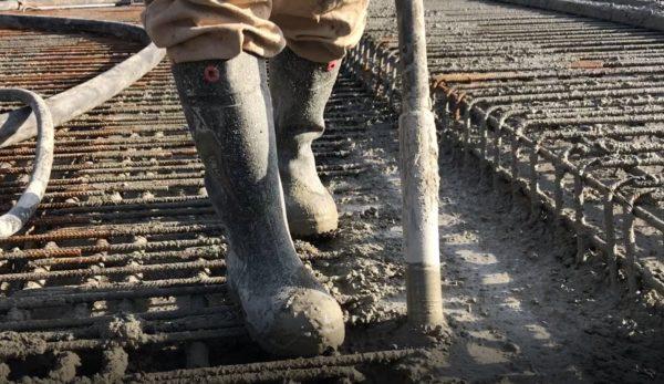 Laarzen_op_ijzervlechtwerk_beton_storten_de_luwte_met_trilnaald_intrillen