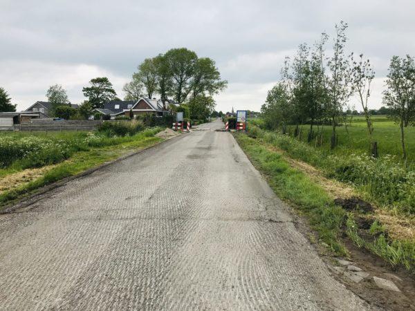 Asfalt_is_gefreesd_weg_landbouw_bomen_aan_weerszijden