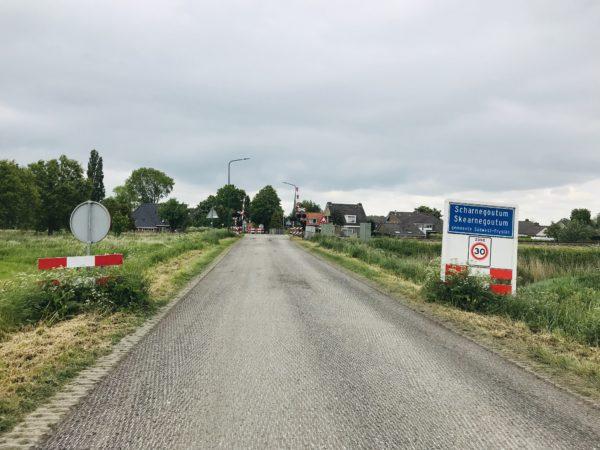 Plaatsnaambord_Scharnegoutum_frezen_landweg_asfalt_slagbomen_treinspoor_rails