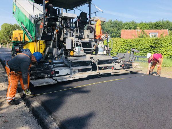 Mannen_met_meetlint_meten_breedte_weg_met_asfaltspreidmachine